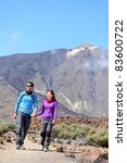 Couple hiking outdoors in nature. Happy young couple hikers walking outside in dramatic mountain landscape on volcano Teide, Tenerife, Canary Islands. - stock photo