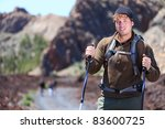 Adventure hiking man. Portrait in mountain landscape. Caucasian male hiker smiling in nature standing with hiking poles in volcano landscape on Teide, Tenerife, Canary Islands - stock photo