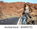 Travel woman hitchhiking. Beautiful young female hitchhiker by the road during vacation trip on Volcano Teide, Tenerife, Canary Islands. - stock photo