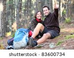 Young happy couple hiking in forest. Smiling couple resting enjoying a break during hike vacations. Caucasian man model. Asian woman model. - stock photo