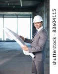 Businessman holding on-site plan - stock photo
