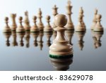 Light colored, wooden pawn in front of other chess pieces. - stock photo