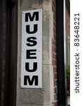 Museum Sign against Stone Wall ay Building Entrance - stock photo