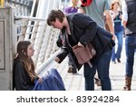 Small photo of LONDON-APRIL 25: A unidentified woman gives money to a young homeless woman on Charing Cross Bridge on April 25, 2010 in London, UK. Homelessness in England had risen by 42% in 2010 to 1,768, from 1,247 in 2009.