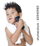 A young boy has fun pretending to shave with an electric razor. - stock photo