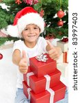 Happy boy with christmas hat and presents giving thumbs up sign - stock photo