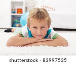 Beautiful kid resting on the floor propping his head - stock photo