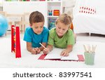 Kids doing math exercises to be in shape for the school - laying on the floor - stock photo