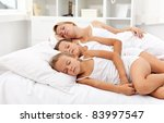 Nice summer siesta - woman and kids laying in bed having a nap - stock photo