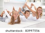 Family doing stretching exercises laying on the floor - healthy lifestyle - stock photo