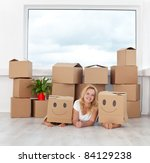 Happy people having fun in a new home with cardboard boxes and a plant - stock photo