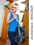 attractive housewife holding vacuum cleaner in her home - stock photo
