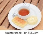 Close up a cup of tea and swiss roll with condensed milk cream on wood pattern - stock photo