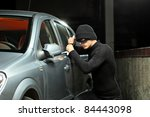 A thief with a robbery mask trying to steal an autobmobile - stock photo