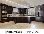 Stock photo large kitchen in luxury home with dark wood cabinetry 84447223