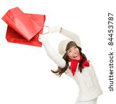 Winter and christmas shopping. Woman holding red shopping bags happy, ecstatic and cheering with energy, Isolated on white background. - stock photo