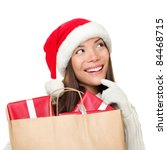 Christmas shopping woman thinking wearing santa hat and holding gifts in shopping bag. Thinking mixed race Chinese Asian / Caucasian female looking sideways smiling happy isolated on white background. - stock photo