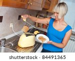 attractive housewife using toaster in her kitchen - stock photo