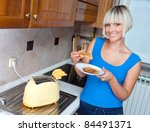 attractive housewife eating toast in her kitchen - stock photo