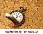 A pocket watch rests on a golden puzzle. - stock photo