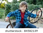 happy 7 yr old boy having fun sitting on old farm tractor, plaid jacket and jeans - stock photo