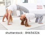 Healthy life education by example - woman and little girl exercising together - stock photo