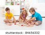 Three kids playing with wooden blocks sitting on the floor - stock photo