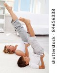 Healthy life education by example - little boy and his mother exercising at home - stock photo