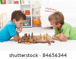 Kids playing chess laying on the floor and thinking intensely - stock photo