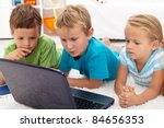 Serious and focused kids looking at laptop computer laying on the floor - stock photo