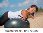 Plus Size Female Exercise Outdoor on Fitness Ball in water front - stock photo