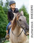 Horseback riding - little girl is riding a horse - stock photo