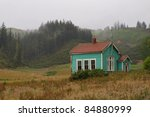 Old wooden school building in clouded countryside - stock photo