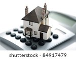 House resting on calculator concept for mortgage calculator, home finances or saving for a house - stock photo