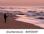 Lone fisherman on the beach at sunrise - stock photo