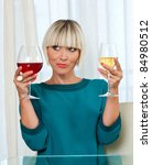 attractive woman choosing from red and white wine - stock photo