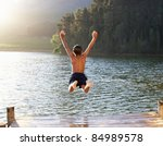 young boy jumping into lake | Shutterstock . vector #84989578