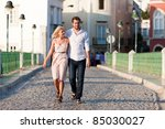 Small photo of Couple having a city break in summer walking on a bridge over a river in the evening light