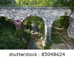 Center view of old stone bridge with red vine built in 1874 - stock photo