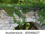 Keystone view of old stone bridge built in 1874 with close up of Virginia Creeper - stock photo