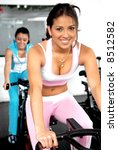 girls cycling and working out at the gym - stock photo
