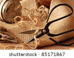 Rustic still life of traditional hand forged scissors with twine dispenser and burlap.  Macro with shallow dof. - stock photo