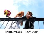 A bride and groom on a balcony - stock photo