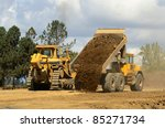 A large track bulldozer and a large articulating dump truck at a new road project in Oregon - stock photo