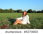 Young sexy woman sitting on the grass - stock photo