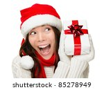 Christmas woman holding present excited. Young happy woman wearing santa hat looking to side showing Christmas gift isolated on white background. Beautiful young santa woman. - stock photo
