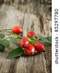 Autumn still-life with red field rose on wooden background - stock photo