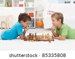 Two Boys Playing Chess Laying...