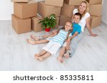 Happy people in their new home laying on the floor smiling - stock photo