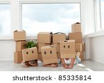 Family having fun with cardboard boxes moving into their new home - stock photo